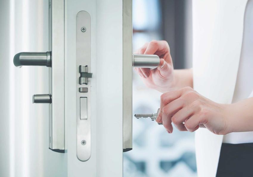 Kobieta otwierająca drzwi, a także informacje, jak rozpoznać drzwi prawe, a jak rozpoznać drzwi lewe po układzie klamki