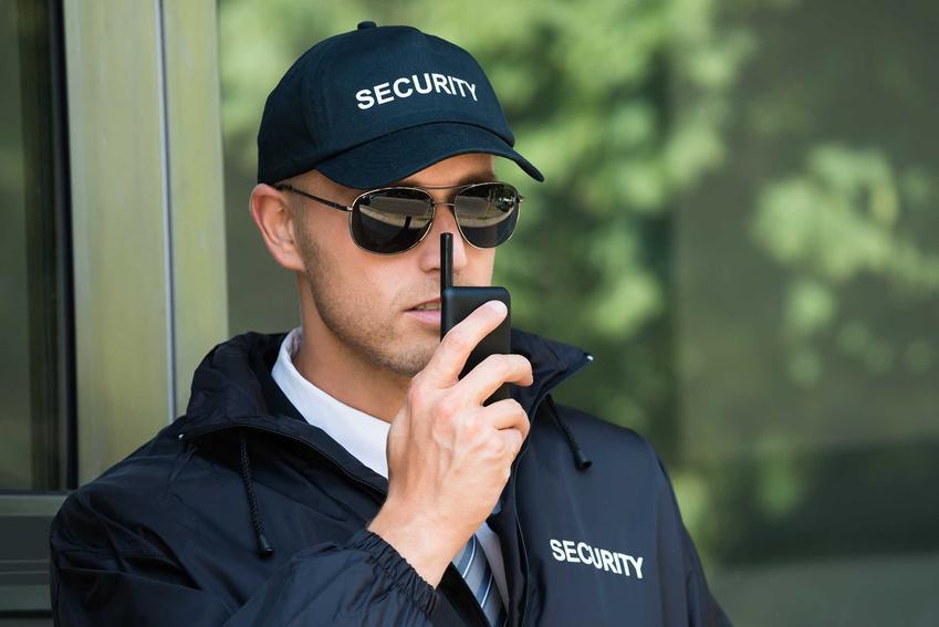 Pracownik firmy ochroniarskiej z krótkofalówką w dłoni ubrany w strój służbowy na tle budynku o dużych oknach