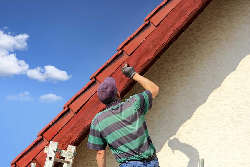 Impregnacja dachu z czerwonej blachy przez mężczyznę z pędzlem w czapce na głowie stojącego na drobinie przy krawędzi dachu