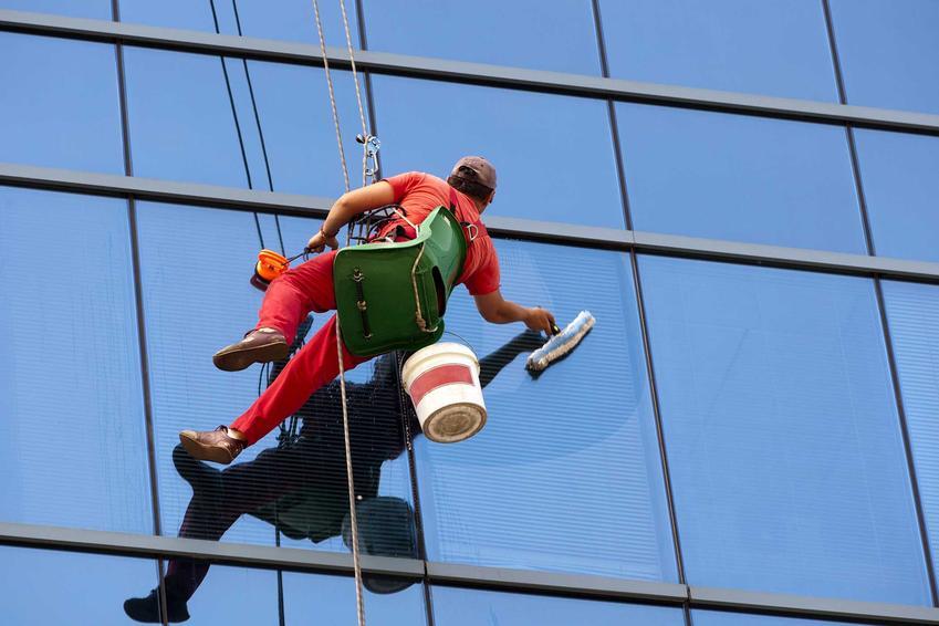Mycie okien na wysokości przez człowieka uwiązanego na linach i uprzęży alpinistycznej, zajętego myciem okien na szklanym biurowcu