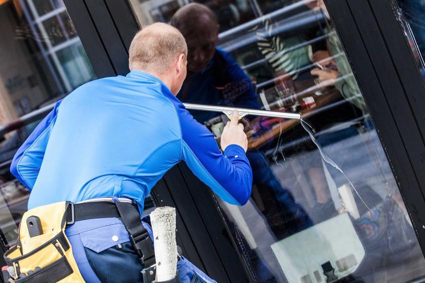 Mycie witryny w restauracji przez mężczyznę ściągaczką do wody, który wykonuje usługi płatnego mycia okien w miejscach publicznych