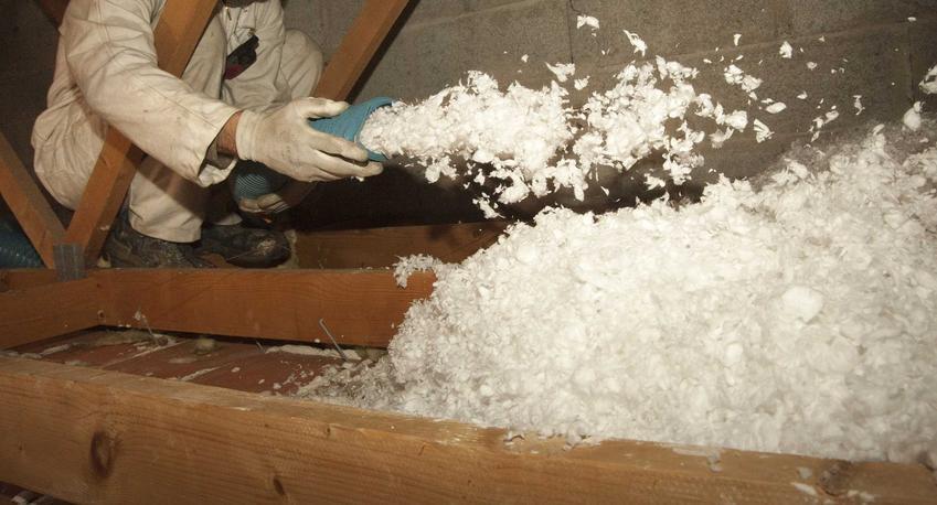 Ocieplanie stropu ekofibrem sypanym ze specjalnego urządzenia przez mężczyznę stojącego na strychu