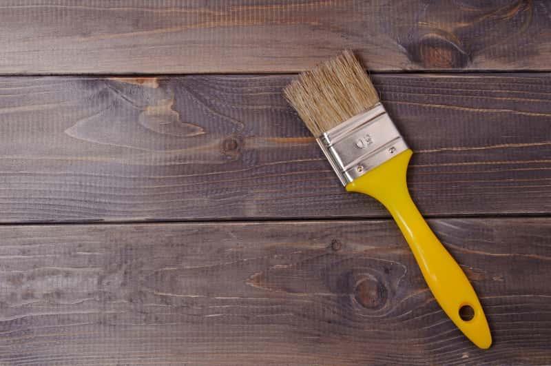 Pędzel leżący na drewnie malowanym farbą wodną, a także informacje o farbach wodnych do drewna, ceny, opinie oraz zastosowanie