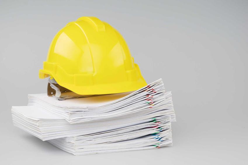 Prawo budowlane symbolizowane przez stos dokumentów spętych spinaczami pod żółtym kaskiem budowlanym na szarym tle
