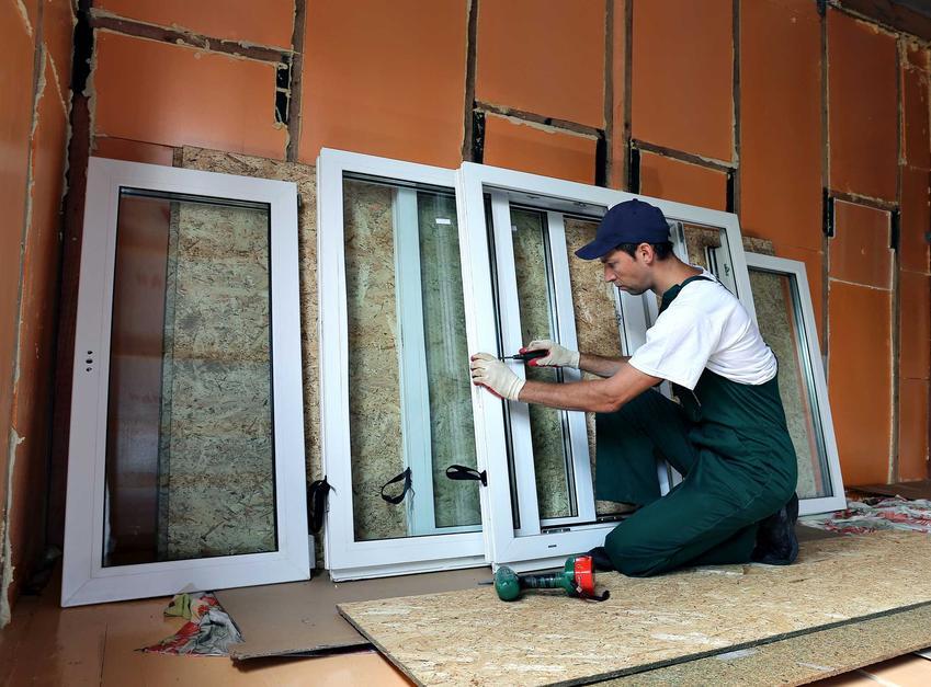 Renowacja okien drewnianych przez specjalistę w stroju roboczym. Konserwacja okien drewnianych to gwarancja, że będą bardziej trwałe