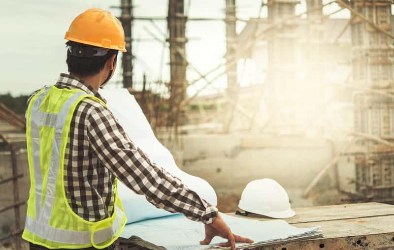 Inżynier w białym kasku na placu budowy, a także jak zdobyć uprawienia budowlane i uprawnienia SEP, a także najważniejsze ingormacje