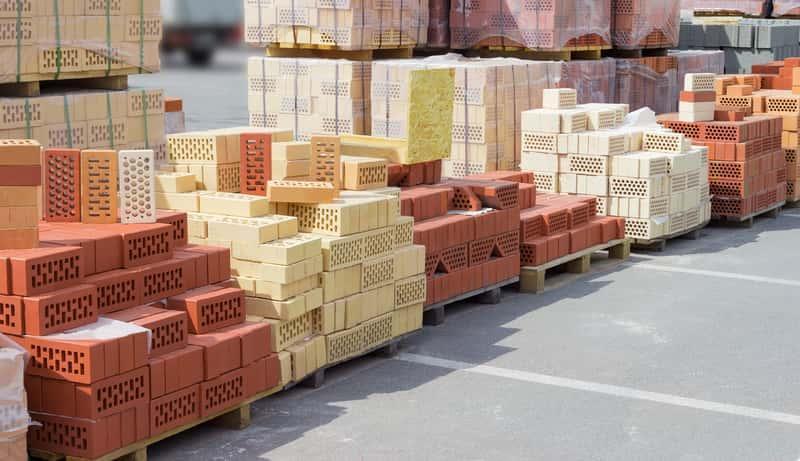 Cegły różnego rodzaju leżące w składzie budowlanym, a także wymiary cegły klinkierowej, kratówki oraz cegły pełnej