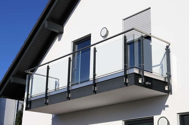 Szklana balustrada na balkonie przy nowoczesnym domu, a także ceny, rodzaje balustrad i barierek, porady przy zakupie