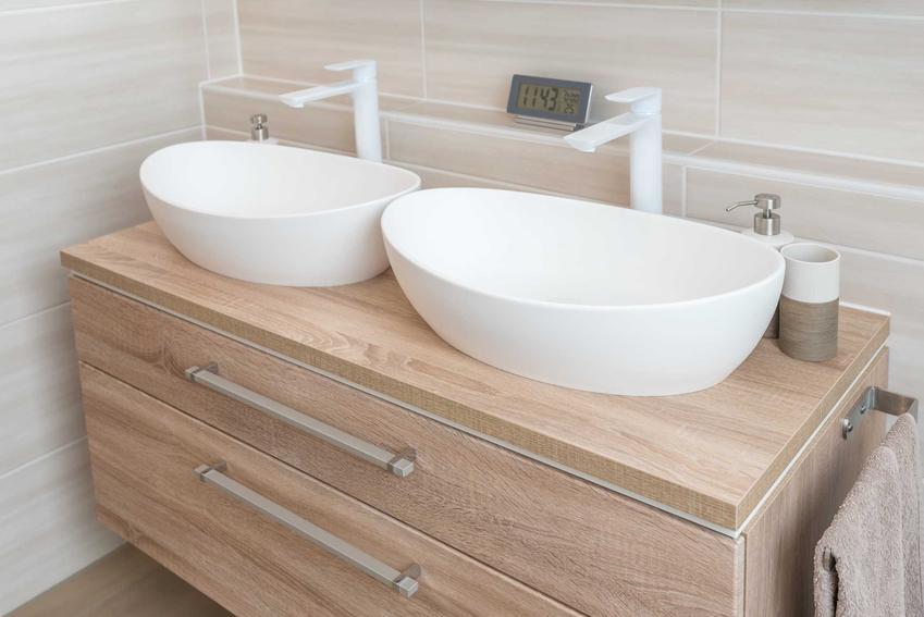 Umywalki nablatowe na standardowej wysokości w bardzo nowoczesnym stylu na drewnianej komodzie łazienkowej na tle kremowych płytek