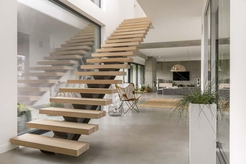 Nowoczesne drewniane schody samonośne umieszczone w minimalistycznym wnętrzu, a także cena, zasady konstrukcji, montaż
