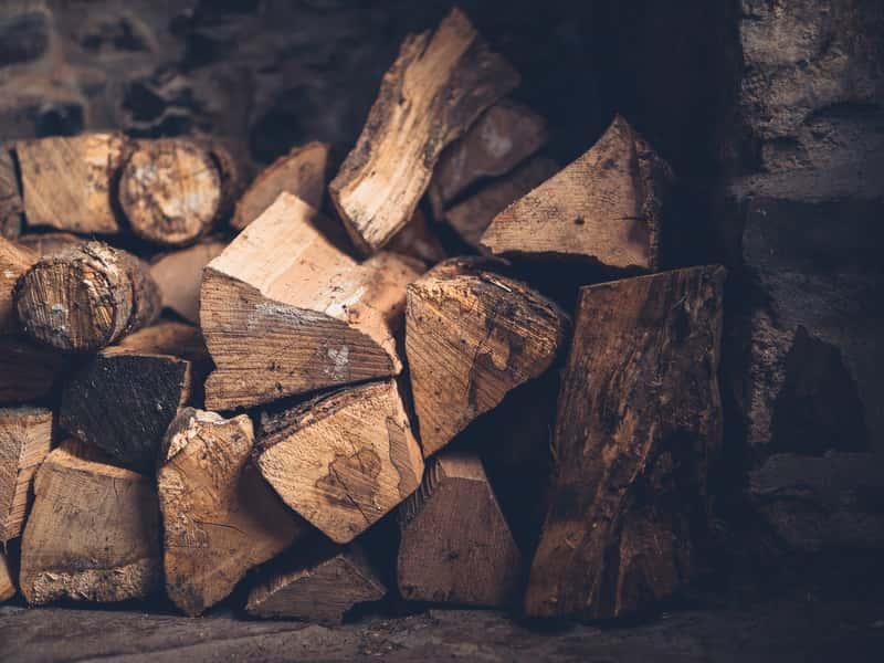 Ułożone drewno kominkowe na stosie, a także cena w różnych miastach, najlepsze rodzaje drewna kominkowego i wybór drewna do kominka