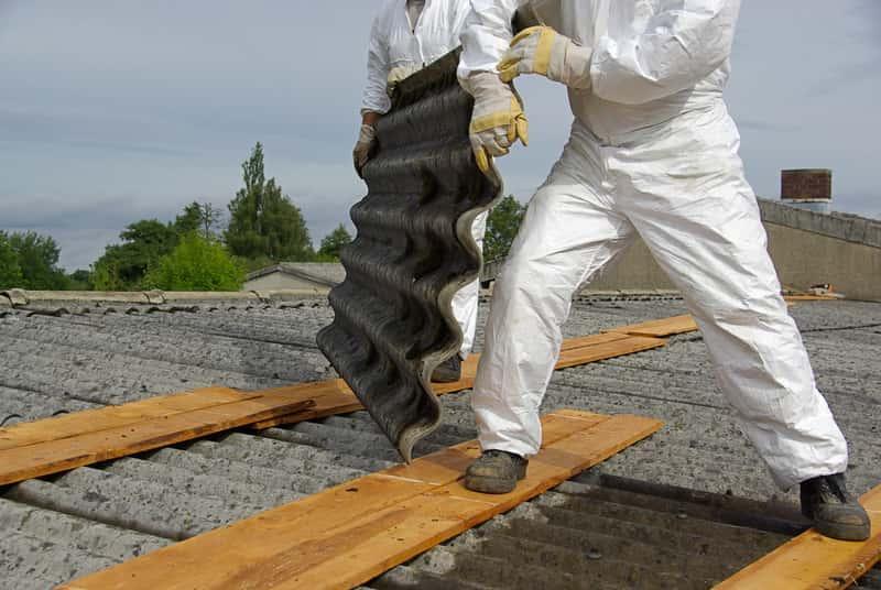 Azbest na dachu ściągany przez robotników, a także informacje o tym, do kiedy ma zniknąć azbest z polskich dachów