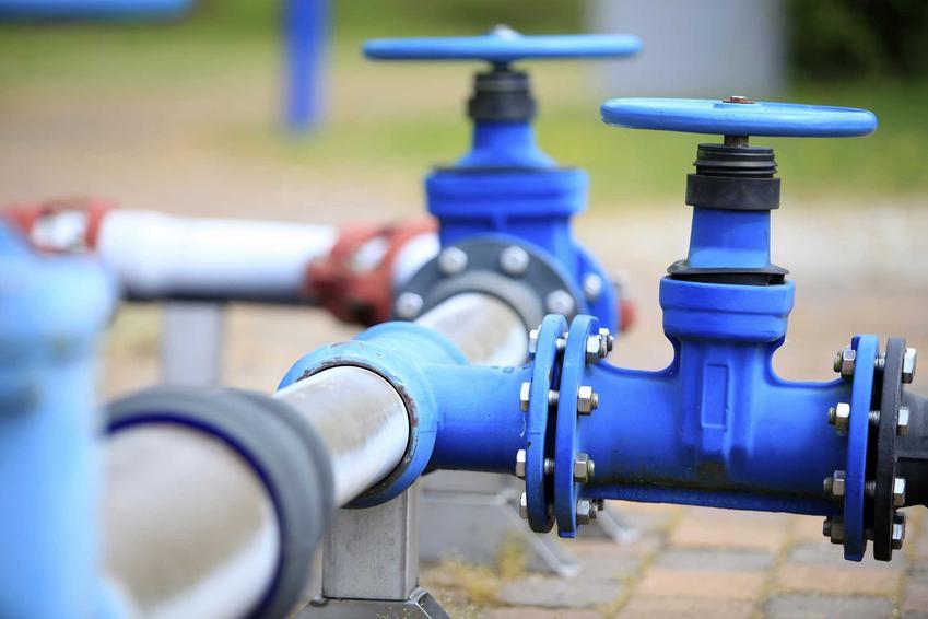 Przyłącze wodociągowe do działki budowlanej - rurki w niebieskiem kolorzez zaworami widoczne nad kostką brukową, z zielenią w tle