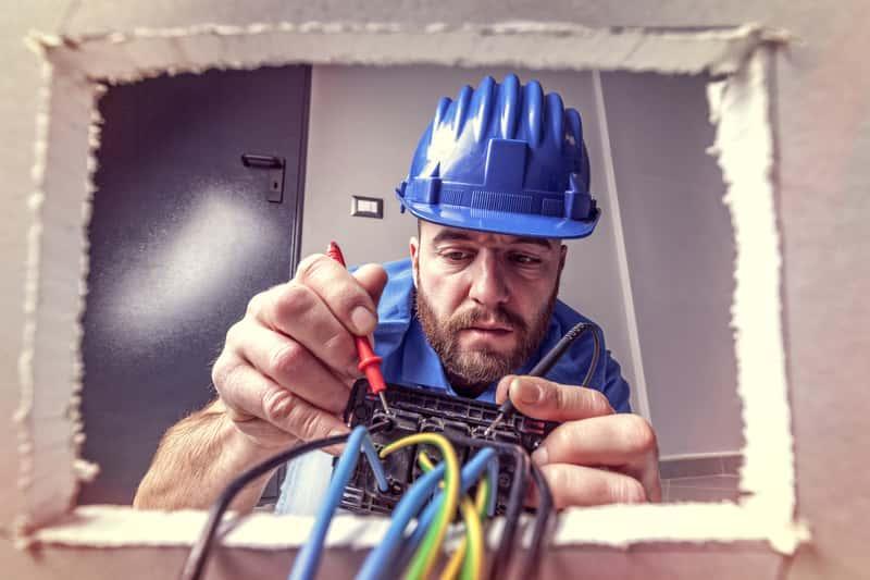 Mężczyzna zajmujący się instalacją wyłącznika różnicowoprądowego w mieszkaniu, a także ceny, zasady działania i zastosowanie