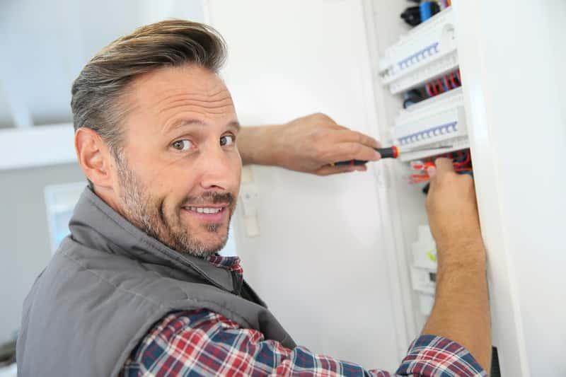 Mężczyzna naprawiający przekaźnik bistabilny w skrzynce elektrycznej, a także zastosowanie, cena, zasada i sposób działania