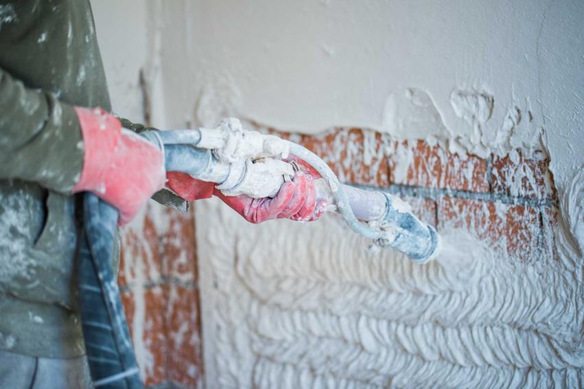 Tynk maszynowy nakładany na ceglaną ścianę przez specjalistę - mężczyznę ubranego w strój roboczy i rękawice ochronne