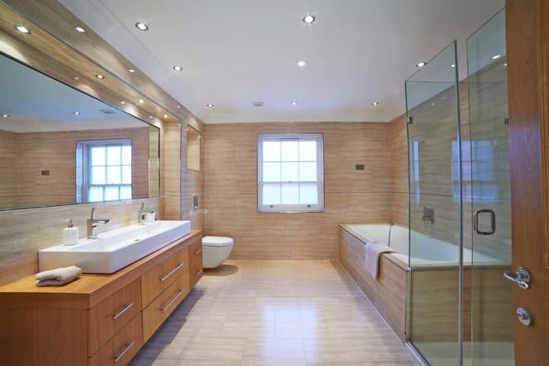 Nowoczesna łazienka w neutralnych kolorach z wykończeniem drewnianym, a także TOP 10 pomysłów na łazienki