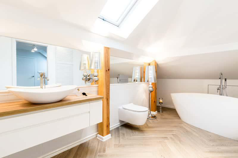 Biała łazienka z drewnianymi akcentami i oknem dachowym na poddaszu, a także 10 aranżacji łazienki