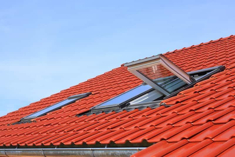 Okna dachowe na budynku z czerwonym dachem, a także obróbka okna dachowego krok po kroku do osadzenia w dachu
