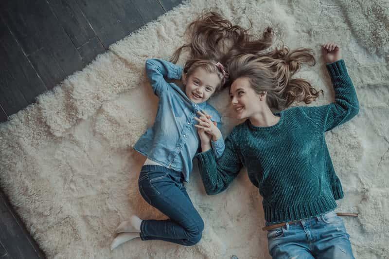 Kobieta i dziewczynka leżące na grubym dywanie w białym kolorze z firmy Kowary, a także najlepsze modele, ceny i rodzaje