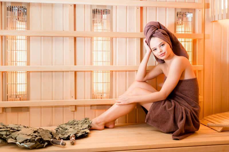 Kobieta siedząca w saunie suchej, a także informacje o saunie na podczerwień (sauna sucha) oraz zalety, wady, działanie oraz właściwosci