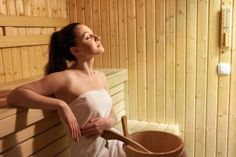 Kobieta zawinięta w ręcznik siedząca w saunie, a także temperatura, wilgotność i najwazniejsze zasady, jak korzystać z sauny