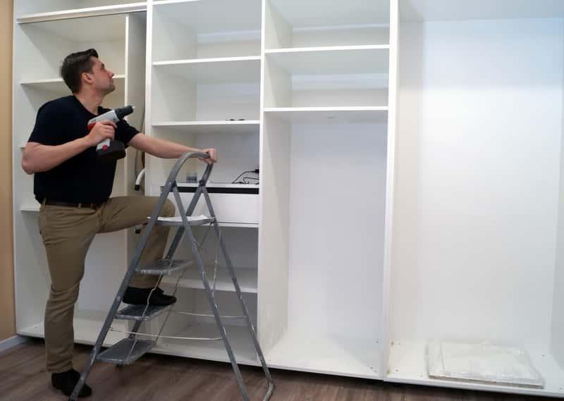 Mężczyzna podczas montażu zabudowanej szafy wnękowej, a także szafy wnękowe na wymiar, opinie, ceny, zastosowanie