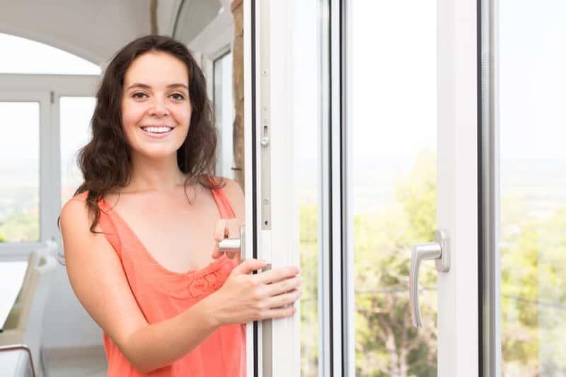 Kobieta stojąca przy białym oknie, a także inne modne kolory okien PCV - biel, złoty orzech, antracyt, kolory typowe dla drewna