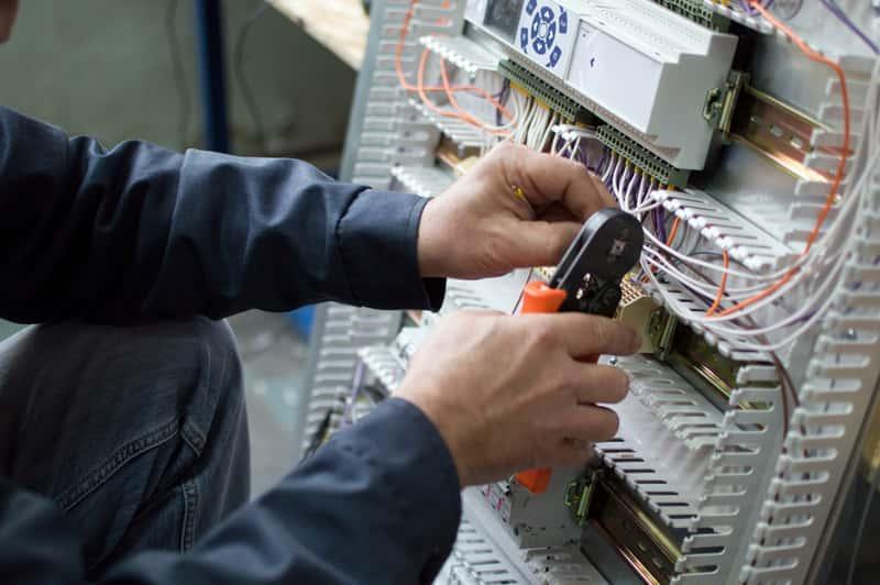 Elektryk podczas montażu szafy elektrycznej, a także szafa elektryczna i jej zastosowanie, producenci, opinie oraz ceny