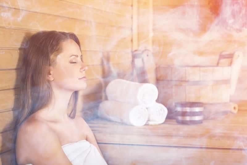 Kobieta siedząca w saunie mokrej, a także najważniejsze informacje, zalety, wady, właściwości, porady dla użytkowników