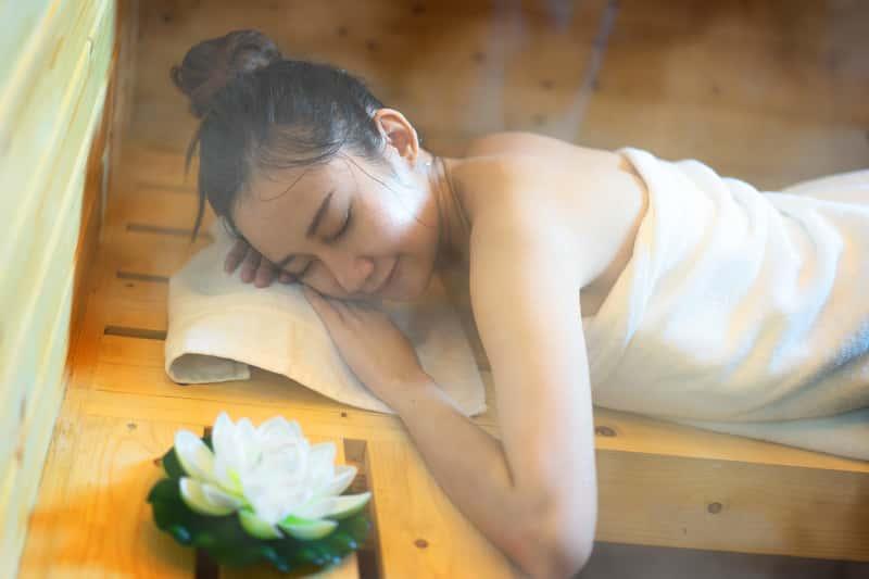 Kobieta wypoczywająca w saunie, wdychająca zapach olejku do sauny, a także ich cena, olejki eteryczne, relaksujące, rodzaje i zastosowanie