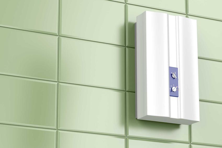 Przepływowy podgrzewacz wody Siemens na tle zielonych płytek w łazience. Podgrzewacz przepływowy Siemensa to jeden z popularniejszych produktów tego typu
