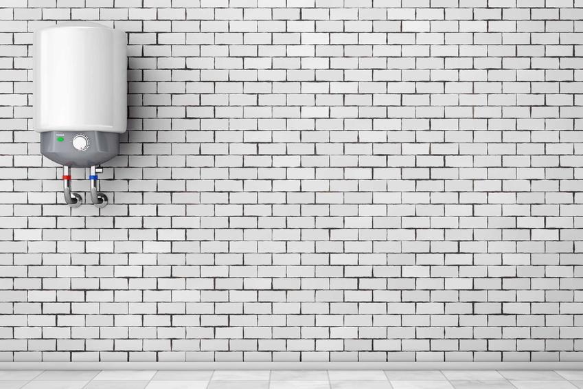 Podgrzewacz wody Ariston na tle ceglanej białej ściany. Pojemnościowy elektryczny podgrzewacz wody to popularne rozwiązanie.