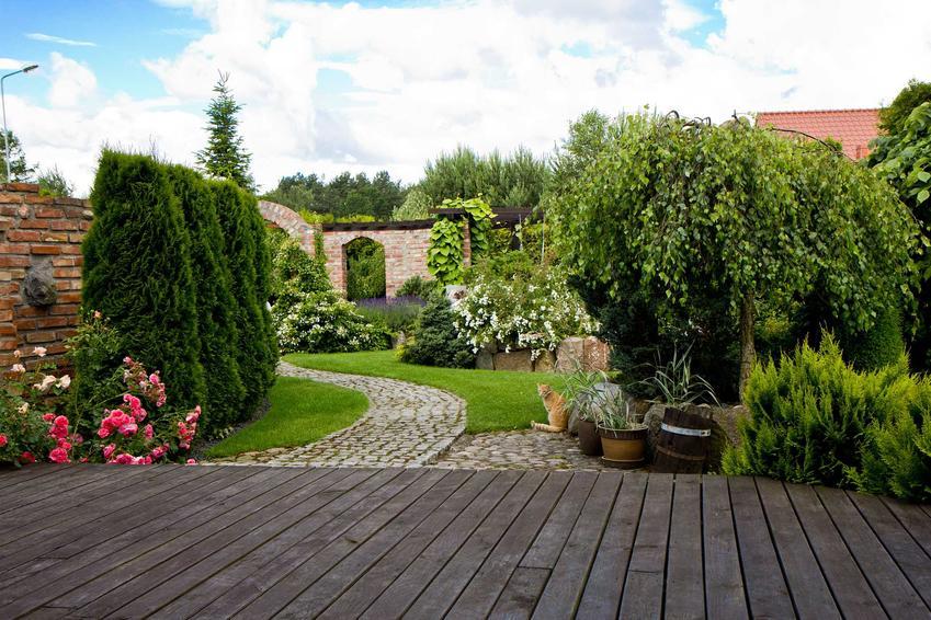 Taras kompozytowy na tle pięknego ogrodu. Taras z kompozytu drewnopodobne jako alternatywa dla betonu i drewna