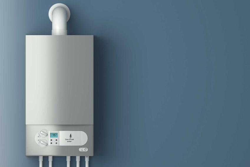 Gazowy podgrzewacz wody z zamkniętą komorą spalania na tle szarej ściany