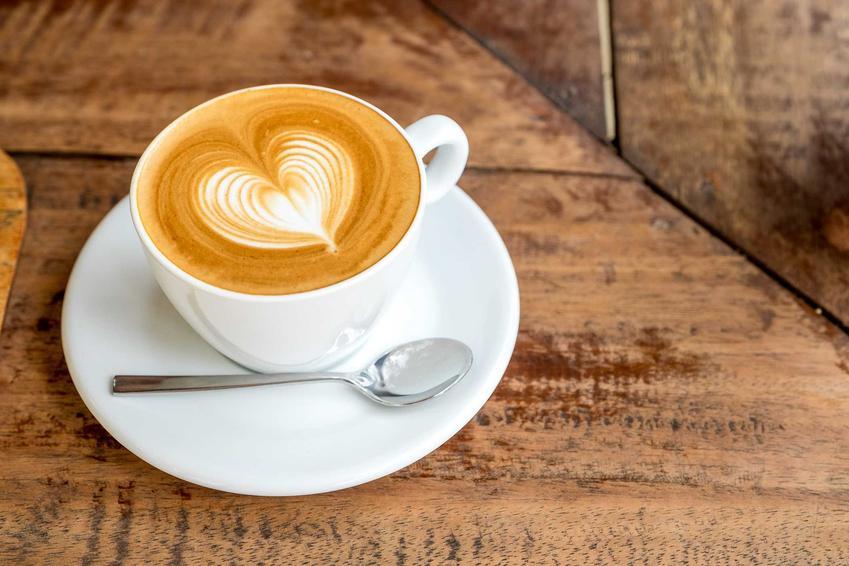 Kawa w białej filiżance z serduszkiem z mleka. Ekspres ciśnieniowy DeLonghi to urządzenie, które umożliwi jej przygotowanie.