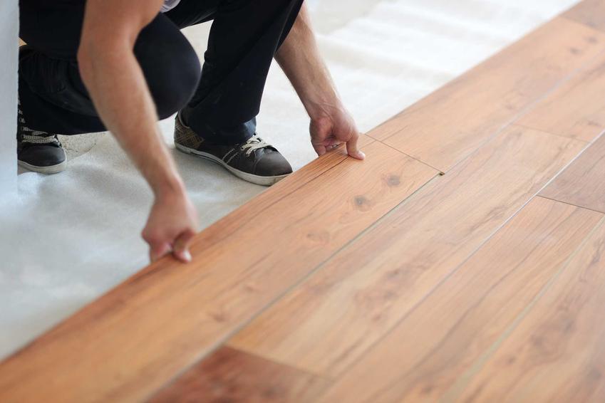 Mężczyzna podczas układania peneli podłogowych z Castoramy oraz ceny paneli podłogowych i najpopularniejszych wzorów