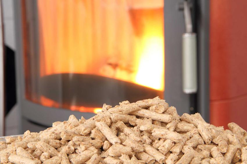 Pellet z ogniem w piecu w tle oraz ceny pieców na pellet w zależności od ich rodzaju a także ceny, popularne modele i rozwiązania oraz porady