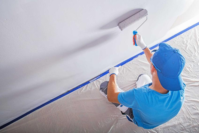 Mężczyzna podczas malowania ściany na biało. Farba ceramiczna oraz jej możliwości zastosowania i ceny.