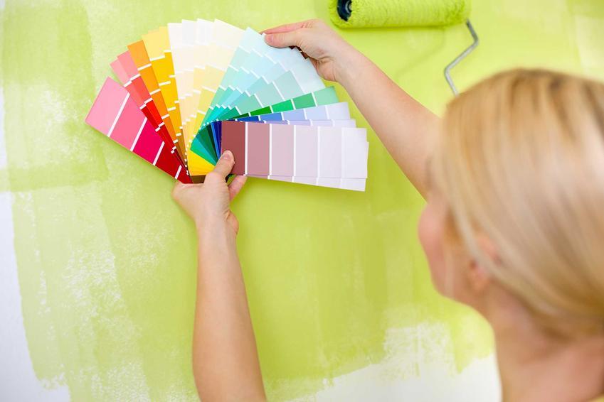 Paleta barw na tle malowanej ściany trzymana przez kobietę. Farby Luxens i ich rodzaje, ceny oraz zastosowanie