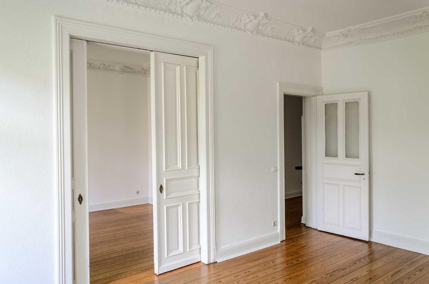 Białe drzwi przesuwne w salonie oraz porady, jaka kaseta do dzrwi przesuwnych będzie odpowiednia, cena i zastosowanie kasety