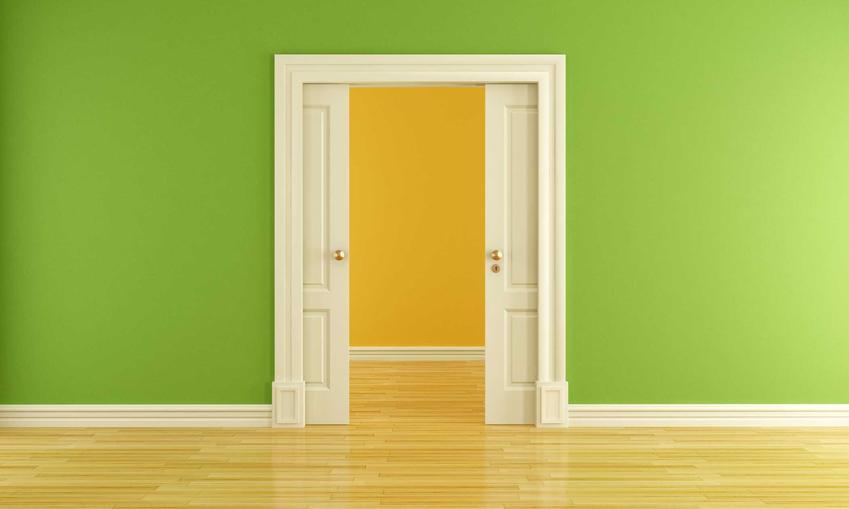 Drzwi przesuwne z kasetą na tle zielonej ściany. Porady, jaka kaseta do drzwi przesuwnych będzie odpowiednia oraz ceny i zastosowanie