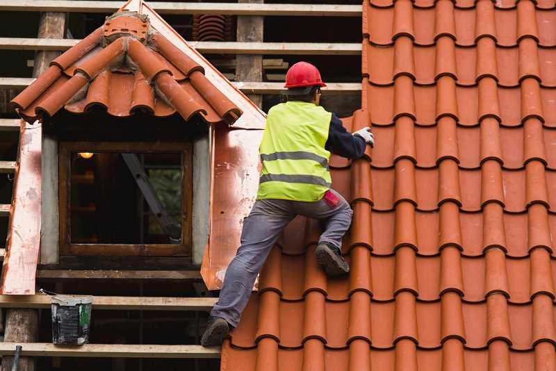 Dachówki ceramiczne układane przez robotnika na dachu, a także informacje o dachówkach betonowych i blachodachówkach krok po kroku