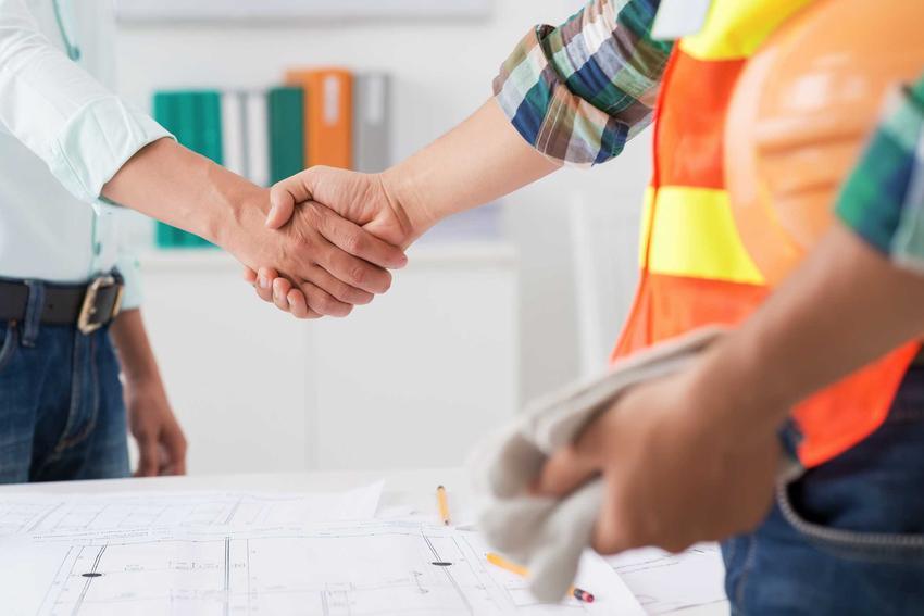 Protokół przekazania placu budowy czy też terenu budowy oraz mężczyźni ściskający sobie dłonie - porady praktyczne