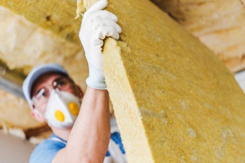 Wełna mineralna twarda podczas montażu przez mężczyznę w masce oraz zastosowanie wełny fasadowej krok po kroku