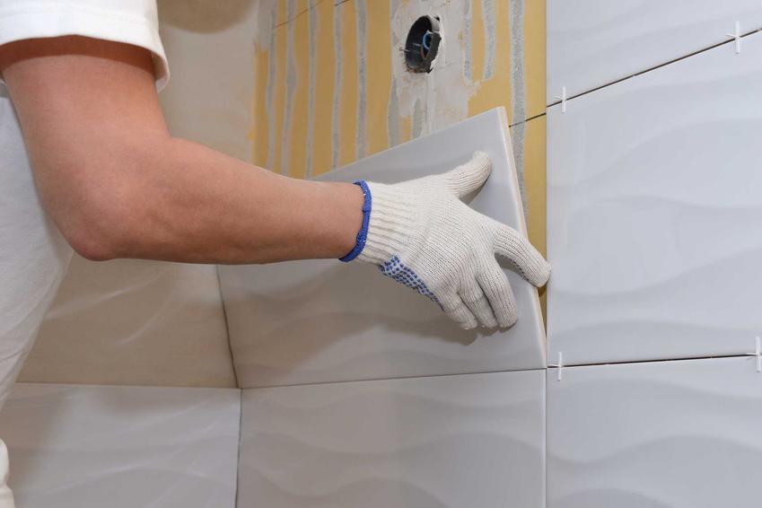 Płytki ścienne podczas układania przez mężczyznę oraz polecane płytki ceramiczne na ścianę -rodzaje, zalety, ceny