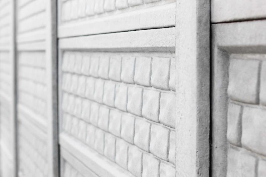 Płot betonowy z prefabrykatów w standardowy wzór w zachodzące na siebie cegiełki zrobiony z trzech części osadzonych na słupkach