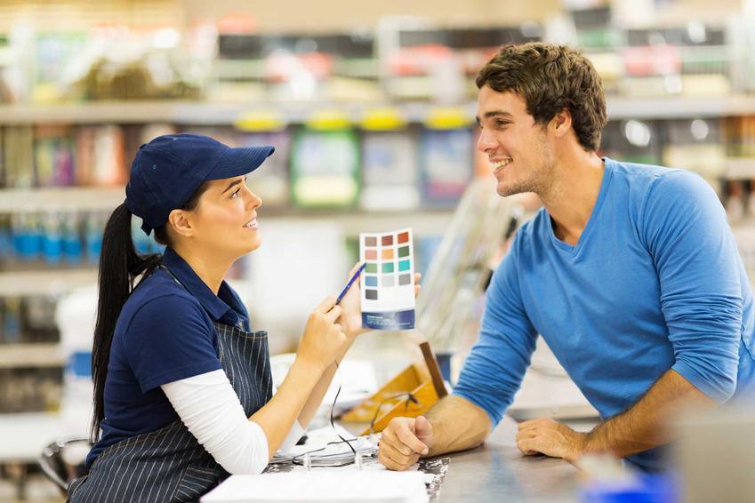 Farby Flugger i paleta kolorów prezentowana mężczyźnie przez ekspedientkę w sklepie, a także ich rodzaje