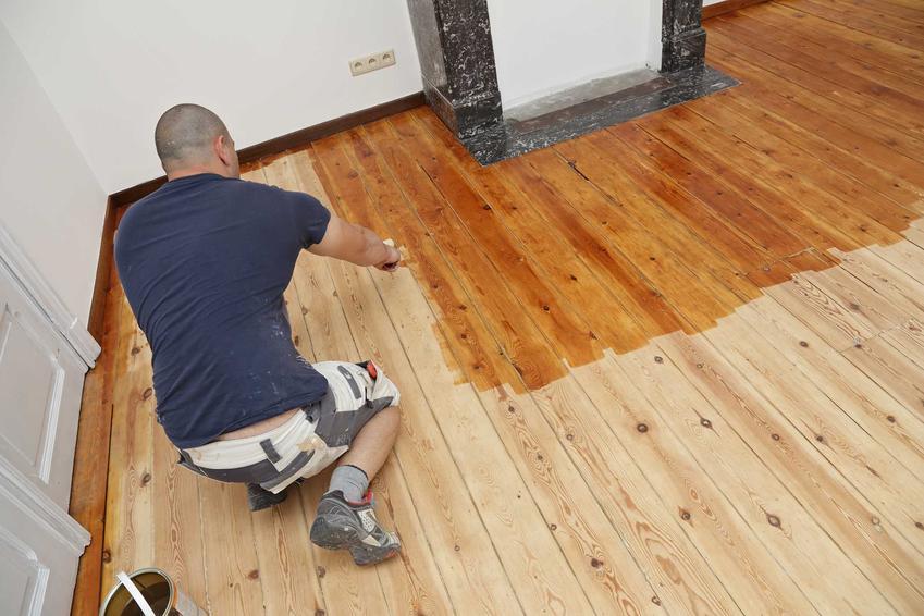 Olejowanie podłogi drewnianej przez mężczynę oraz olejowanie parkietu krok po kroku, najlepsze preparaty oraz zastosowanie