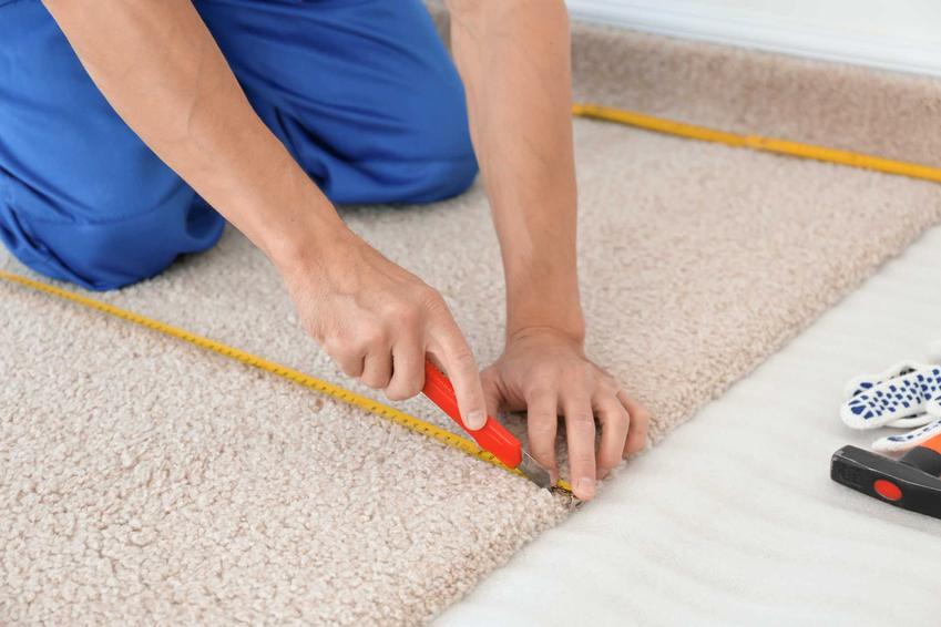 Przycinanie i układanie wykładziny dywanowej przez mężczyznę oraz montaż, czyli kładzenie wykładziny dywanowej krok po kroku